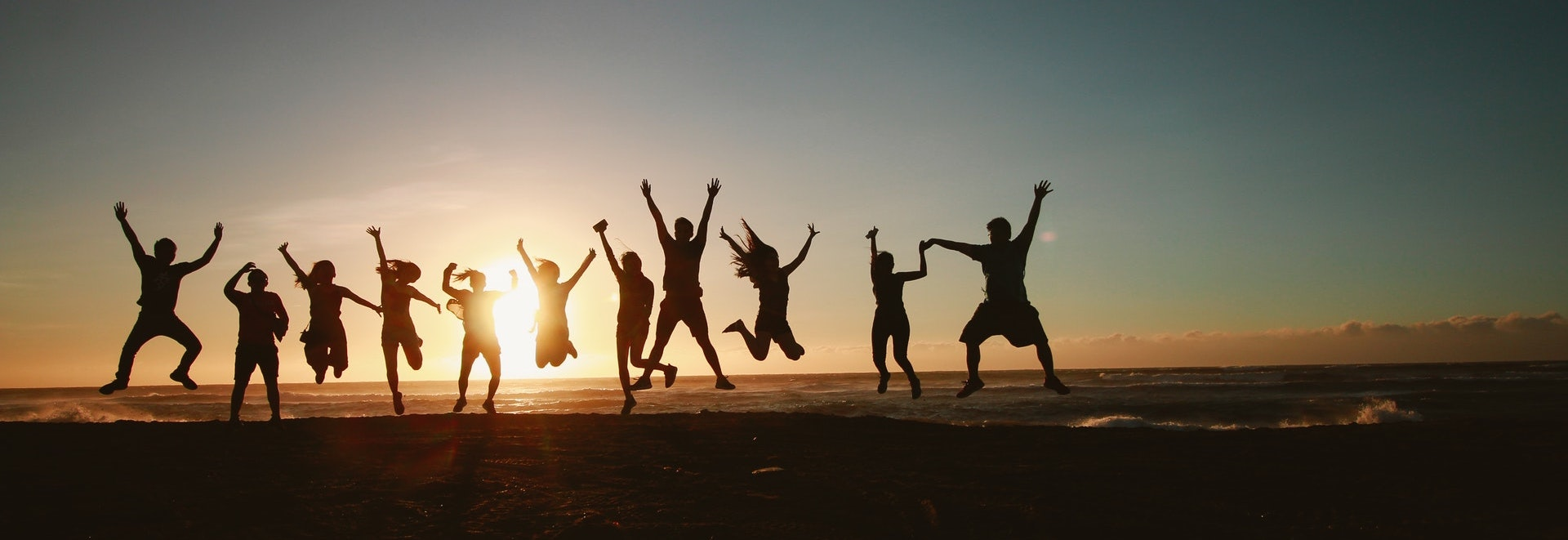 people jumping with sunset background